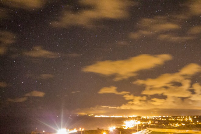 Northern shoreline of Sao Miguel at night. The bright lights in the lower left are headlights.